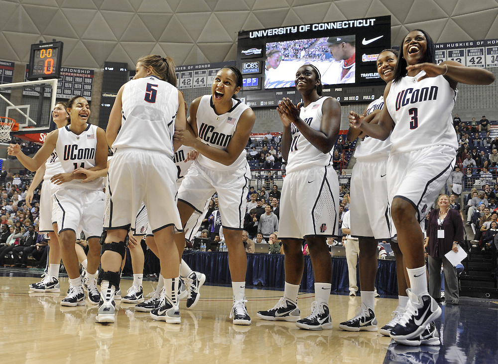 """Connecticut's women's basketball team reacts as teammate Lorin Dixon competes in a final round of the game """"Simon Says"""" during First Night NCAA collegebasketball exhibition, in Storrs, Conn., Friday, Oct. 15, 2010. (AP Photo/Jessica Hill)"""