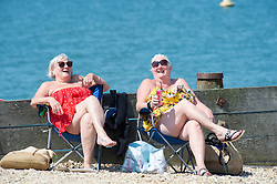 © Licensed to London News Pictures 22/07/2021. Whitstable, UK. Two friends sunbathing on the beach. Another hot heatwave day as people enjoy a day out at Whitstable in Kent.  Photo credit:Grant Falvey/LNP