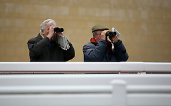 General view of spectators watching though binoculars during the April Meeting at Cheltenham Racecourse