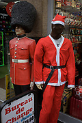Grenadier guardsman mannequin and faceless Santa. Outside a Bureau de Change on London's Oxford Street, we see the two mannequins wearing red costumes - one the uniform of a guardsman soldier in ceremonial dress - and the other a father Christmas character, in front of the tourist trinket shop in the capital's West End.