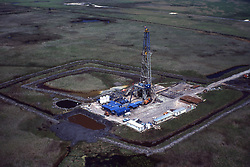 Stock photo of an aerial view of an on-shore drilling operation in a remote grassy area