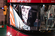 Seen reflected in the windscreen of a passing bus, a government NHS (National Heath Service) ad displays the face of a Covid patient, urging Londoners to stay at home and not to take risks or bend the rules during the third lockdown of the Coronavirus pandemic, at Piccadilly Circus in the capital's West End, on 2nd February 2021, in London, England.