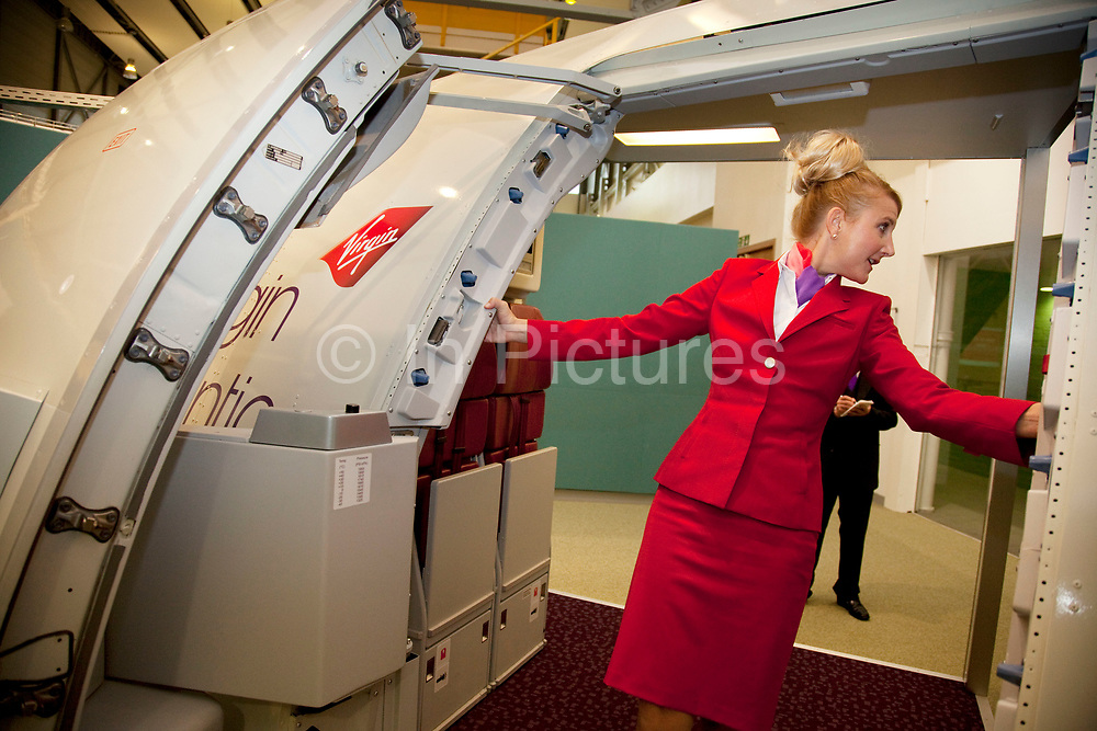Instruction as to how to operate the emergency doors aboard a mock aircraft. Virgin Atlantic air stewardess and steward training at The Base training facility in Crawley. Potential hostesses are put through a gruelling 6 week training program, during which they are tested to their limits. With exams every day requiring an 88% score to pass. The Base is a modern environment for a state of the art airline training situated next to Virgin Atlantic's HQ.