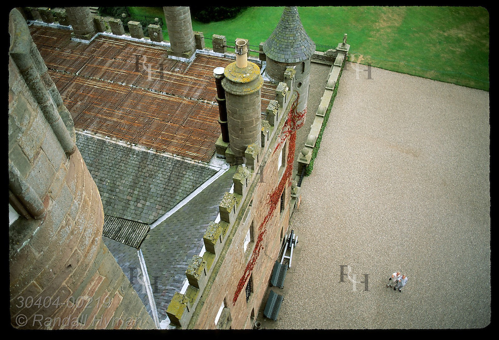 Overview of the front courtyard of Glamis Castle, Queen Mother's childhood home, as two men point upward; Glamis, Scotland.