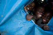 Children look through a hole in a tarp tent at the Shasha IDP site near the town of Shasha, 23km south-west of Goma, Eastern Democratic Republic of Congo on Friday December 12, 2008.
