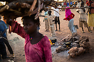 A girl carries firewood she collected through the unaccompanied minors section of the Yida refugee camp. The Lost boys of Sudan may be the best known example of the horror of Sudan's civil war, a conflict that was supposed to end with the independence of the South last July.  Countless South Sudanese boys were forced to flee, separated from their families, walking for days and weeks across hostile lands to the relative safety of a refugee camp. Many died on the way. .Now, this story is repeating itself as thousands of children, separated from their families by constant bombardment, starvation and battles are fleeing the same unresolved conflict, this time in the Nuba mountains of Sudan, where the Khartoum government has been at war with it's own people for over a year. The Sudan government's endless bombing campaigns of civilian targets like schools, churches, markets and boreholes has divided up families and separated children from their parents, and orphaned others..Over 3000 of these children have ended up at the Yida refugee camp, a controversial refuges for the Nuban people close to the North South border that the UN refuses to recognize as a camp for fear of being seen as supporting the rebels. The children have horrific stories. 20 year old John first lost his family in a bombing, he then lost his two younger brothers to starvation, without even the energy to bury them, he walked south for days until he arrived in Yida. 12 year old Rose fled with her entire boarding school after it was bombed and many of here fellow students and teachers killed. Robert watched his family stoned to death after a desperate group of refugees was ambushed by a Northern militia on the border..A few volunteer caretakers and teachers tend to the children. 22 year old Jamina who was separated from her own mother for 11 years during the last war. Today she watches over 500 girls in the same position. Packed into grass huts they built themselves the children try to study, and play and