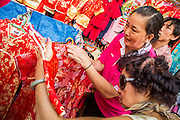 """22 JANUARY 2013 - BANGKOK, THAILAND:   Women shop for new dresses for Chinese New Year at pop up stores on Yaowaraj (Yaowarat) Road, the heart of Bangkok's Chinatown district. Chinese New Year is not an official public holiday in Thailand, but it is one the biggest celebrations in the Bangkok, which has a large Chinese population. Chinese New Year is February 10 this year. It will be the """"Year of the Snake.""""    PHOTO BY JACK KURTZ"""