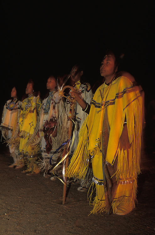 An Apache girl dances together with four other girls at her Sunrise Dance, a first menstruation rite,  on the San Carlos Apache Indian Reservation in Arizona, USA. The girls are all dressed in traditional buckskin clothes. The Sunrise Dance is the most important ceremony of the Apache Indians. It is held during the summer, within one year after the girl has had her first menstruation, and lasts for four days. The rites are supposed to prepare the girl for adulthood and to give her a long and healthy life without material wants.