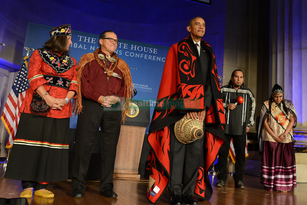 September 26, 2016 - Washington, DC, United States of America - U.S. President Barack Obama smiles wearing a ceremonial blanket given him by Mohegan Chief Lynn Malerba, left, and Brian Cladoosby, President of National Congress of American Indians, during the White House Tribal Nations Conference at the Mellon Auditorium September 26, 2016 in Washington, DC. (Credit Image: © Interior Department/Planet Pix via ZUMA Wire)