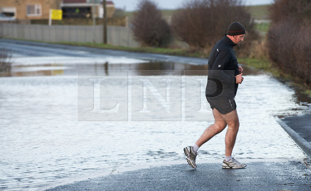 © Licensed to London News Pictures. 27/01/2013..Cleveland, England, UK..Following the recent snowfall a fast thaw through the night brought heavy flooding to some parts of Cleveland and North Yorkshire with many roads closed...A runner decides to turn back rather than run through the flood water on the outskirts of Saltburn...Photo credit : Ian Forsyth/LNP