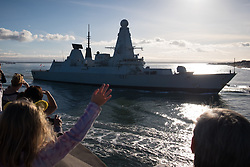 © Licensed to London News Pictures. 25/10/2017. Portsmouth, UK.  People watching and waving as HMS Duncan (D37) approaches the entrance to Portsmouth Harbour today, 25th October 2017. The Type 45 destroyer has been in Portsmouth since September and is believed to be preparing to resume the role as flagship to the Standing NATO Maritime Group 2 (SNMG2) in the Mediterranean Sea, currently being fulfilled by HMS Diamond.  Photo credit: Rob Arnold/LNP