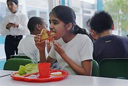 Primary school girl eating dinner in canteen,