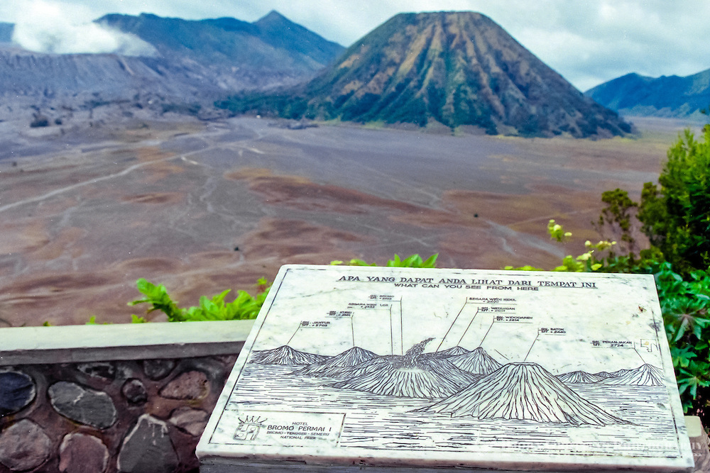 Java, East Java, Mount Bromo. Bromo is a smoking cone inside the huge, older crater Tengger. Gunung Batok to the right of Bromo. Placard with name of mountains.