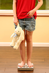 Picture posed by model.<br /> An 11 year old girl using a set of weighing scales.