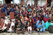The audience watching the performances at the Black-necked Crane festival at Gangte Goemba, Phobjikha Valley, Bhutan. Every year on November 11th, the local community hosts the Black-necked Crane festival at Gangte Goemba, to highlight its significance to the valley. Phobjikha Valley is the most significant overwintering ground of the rare and endangered Black-necked Crane in Bhutan.