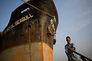 A man pilots a boat past the hull of a large ship in the harbour at Chittagong, Bangladesh