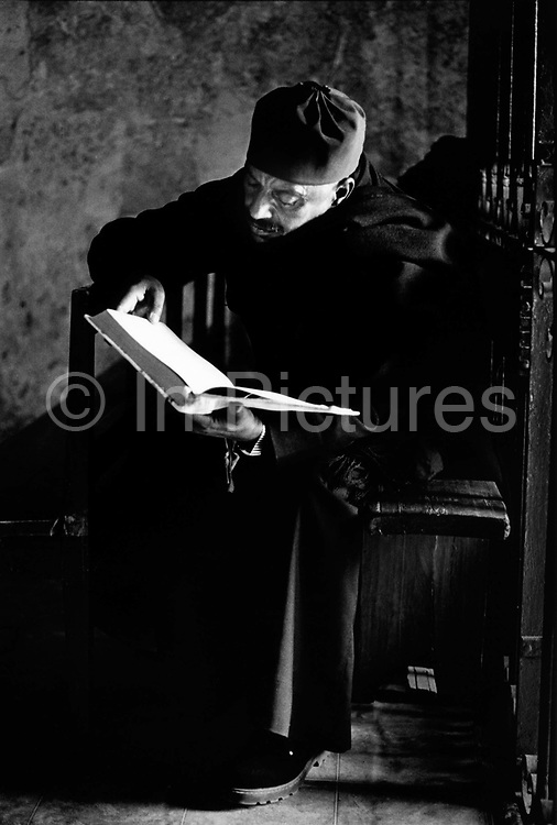A monk reads the bible, Ethiopian Orthodox Monastery built on the roof of the Holy Sepulchre Jerusalem Israel. The Ethiopians have no property in the Hly Sepulchre only access rights and have a small monastery Deir es-Sultan on the roof of a small annex.
