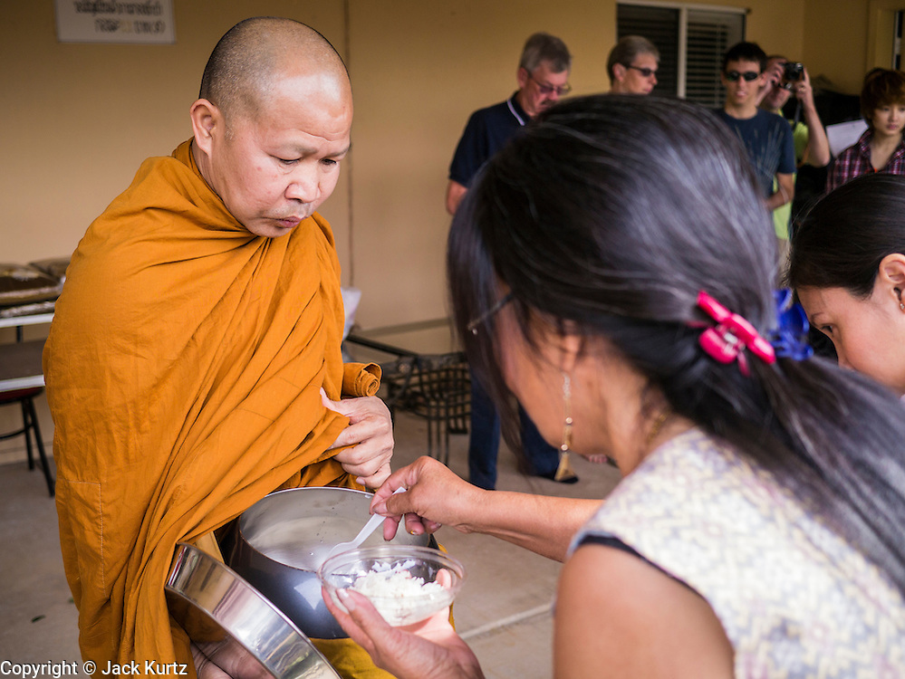"""11 MARCH 2012 - CHANDLER, AZ:     The Abbot at Wat Pa in Chandler, AZ, collects food in his alms bowl during Makha Bucha day services Sunday. Magha Puja (also spelled Makha Bucha) Day marks the day 2,500 years ago that 1,250 Sangha came spontaneously to see the Buddha who preached to them on the full moon. All of them were """"Arhantas"""" or Enlightened Ones who had been personally ordained by the Buddha. The Buddha gave them the principles of Buddhism, called """"The Ovadhapatimokha."""" Those principles are: to cease from all evil, to do what is good, and to cleanse one's mind. It is one of the most important holy days in the Theravada Buddhist tradition. At the temple, people participate in the """"Tum Boon"""" (making merit by listening to the monk's preaching and giving a donation to the temple), the """"Rub Sil"""" (keeping of the Five Precepts including the abstinence from alcohol and other immoral acts) and the """"Tuk Bard"""" (offering food to the monks in their alms bowls). It is a day for veneration of the Buddha and his teachings. It's a legal holiday in Thailand, Laos, Cambodia and Myanmar (Burma).    PHOTO BY JACK KURTZ"""