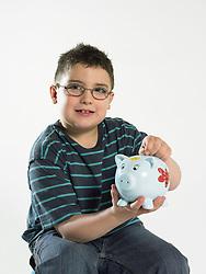 Dec. 14, 2012 - Boy putting coin in piggy bank (Credit Image: © Image Source/ZUMAPRESS.com)