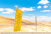 Route 10 along the Egyptian - Israeli border. Looking into Egypt from Israel Yellow Boarder Ahead warning sign in Hebrew Arabic and English