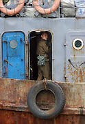 """A North Korean soldier on a boat in the river port town of Sinuiju July 8, 2006. China and North Korea are separated by the Yalu River, upon which Chinese tourists take pleaure cruises across the water to  observe their less economically developed neighbors.  North Korea has threatened to take """"stronger physical actions"""" after Japan imposed punitive measures in response to its barrage of missile tests and pushed for international sanctions. North Korea has vowed to carry out more launches and has said it will use force if the international community tries to stop it. DPRK, north korea, china, dandong, border, liaoning, democratic, people's, rebiblic, of, korea, nuclear, test, rice, japan, arms, race, weapons, stalinist, communist, kin jong il"""