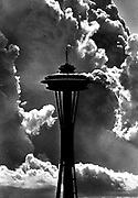 The Space Needle stands tall in the sunshine before a dramatic backdrop of building cumulous clouds. (Peter Haley / The Seattle Times, 1983)