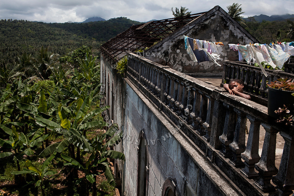 A girl is standing by near her home in Roça Agua Ize', on the island of Sao Tome, Sao Tome and Principe, (STP) a former Portuguese colony in the Gulf of Guinea, West Africa.