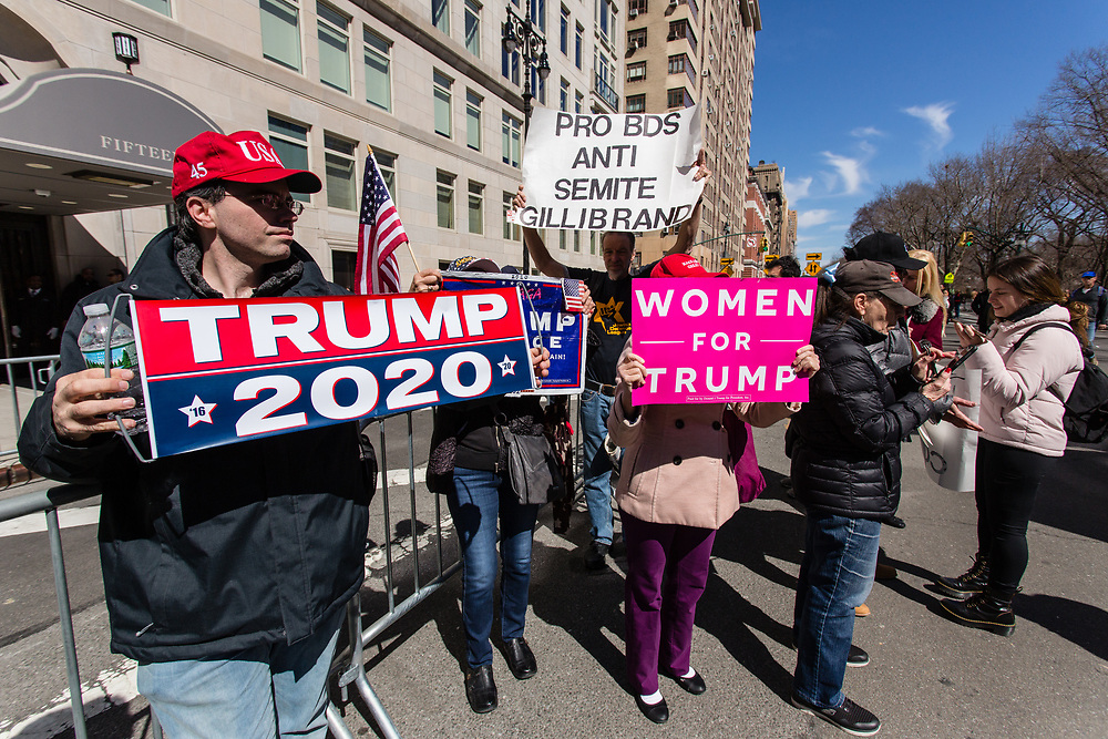 "New York, NY - 24 March 2019. Senator Kirsten Gillibrand (D-NY) held a presidential campaign rally on New York's Central Park West in Front of the Trump Hotel  and Tower. Pro-Trump supporters at the entrance of the rally carry signed reading ""Trump 2020."" ""Women for Trump,"" and ""Pro BDS Anti Semite Gillibrand."" BDS refers to the boycott, divestment and sanctions movement against Israel."