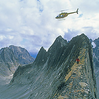 Helicopter flies over mountaineer crossing a narrow arete in the Cirque of the Unclimbables, Yukon Territory, Canada.