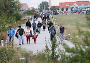 Migrants cross the border into Austria from Hungary September 5, 2015.  Thousands of migrants crossed into Austria, after Hungary's surprise move to take them by bus to the border.