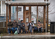 A group of pedestrians use a bus stop shelter to stay dry on Friday, November 1, 2019 on Stedman Street in Ketchikan, Alaska.