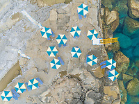 Aerial view of shore of Rhodes island with multicolored parasols and ladder into sea, Greece.