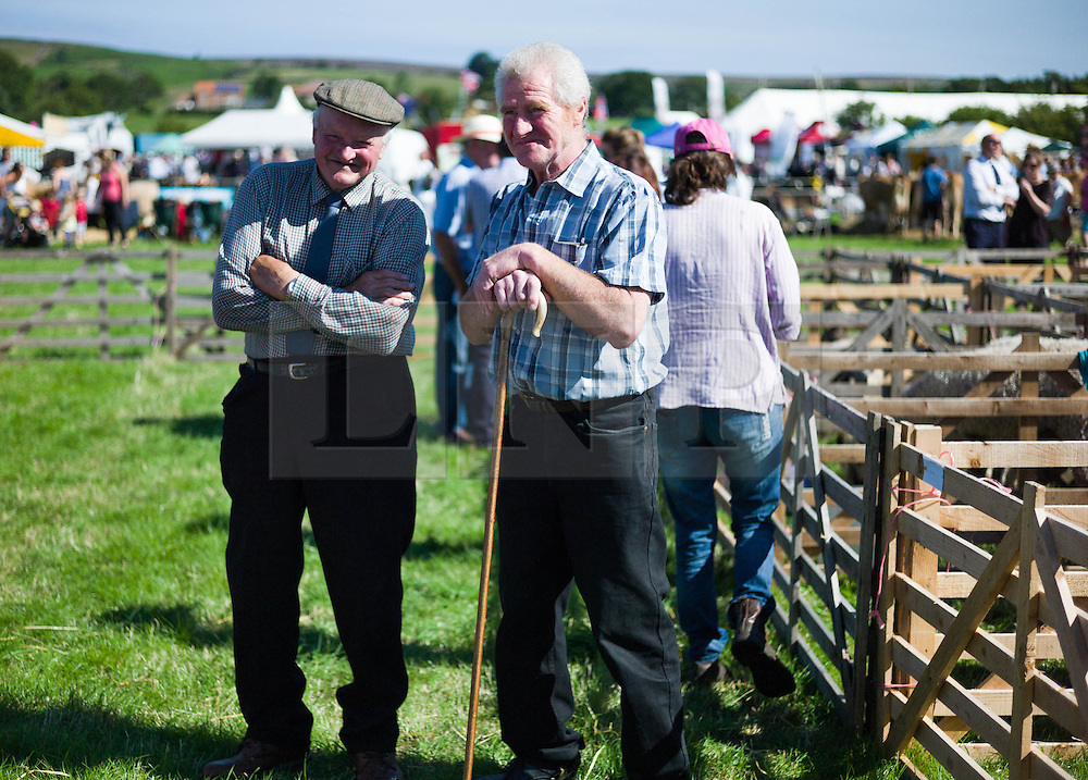 © Licensed to London News Pictures.12/08/15<br /> Danby, UK. <br /> <br /> Two men stand and watch the sheep judging taking place at the 155th Danby Agricultural Show in the Esk Valley in North Yorkshire. <br /> <br /> The popular agricultural show attracts competitors and visitors from all over the surrounding area to this annual showcase of country life. <br /> <br /> Photo credit : Ian Forsyth/LNP