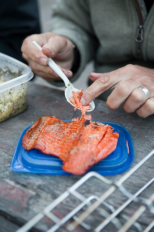 Parmenter Welty uses his fingers as he eats a delicious sockeye salmon filet at a campground on the Copper River near Chitina, Alaska.
