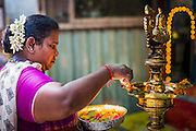 07 JANUARY 2014 - SINGAPORE:   A woman makes an offering at Sri Veeramakaliamman Temple, a Hindu temple located in Little India in the southern part of Singapore. The Sri Veeramakaliamman Temple is dedicated to the Hindu goddess Kali, fierce embodiment of Shakti and the god Shiva's wife, Parvati. Kali has always been popular in Bengal, the birthplace of the labourers who built this temple in 1881. Images of Kali within the temple show her wearing a garland of skulls and ripping out the insides of her victims, and Kali sharing more peaceful family moments with her sons Ganesha and Murugan. The building is constructed in the style of South Indian Tamil temples common in Tamil Nadu as opposed to the style of Northeastern Indian Kali temples in Bengal. PHOTO BY JACK KURTZ