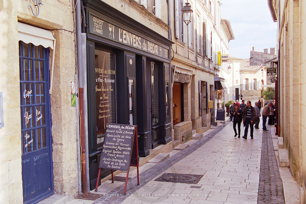 A small pedestrian street in the town of Saint St Emilion, people tourists walking, a restaurant called L'Envers du Decor (the backside of the decoration) with a chalkboard on the street advertising the menu Bordeaux Gironde Aquitaine France Europe
