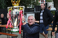 Fans celebrate with the Premier League Trophy outside the stadium and through the city before and during the Premier League match between Liverpool and Aston Villa at Anfield, Liverpool, England on 5 July 2020.