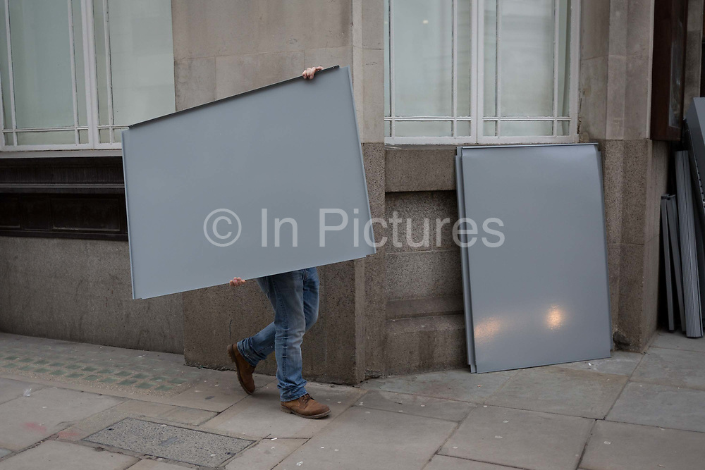 A workman carries a metal panel in a City of London street, on 27th February 2018, in London, England.