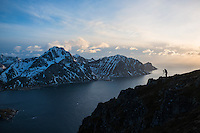 Silhouette of landscape photographer on summit of Offersoykammen with Flakstadoy in background, Lofoten Islands, Norway
