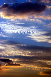 Many different type of clouds fill a dramatic evening sky