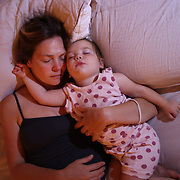 An eighteen month old baby girl is cuddled by her mother while asleep in bed together. Photo Tim Clayton