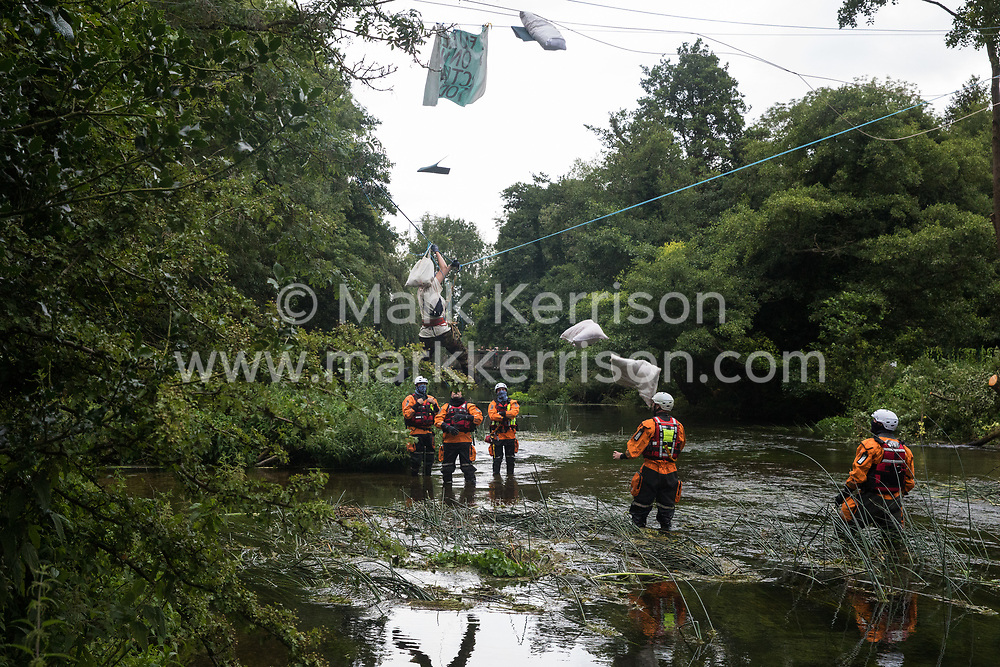 Denham, UK. 24 July, 2020. Swan, an environmental activist from HS2 Rebellion, and her possessions fall suddenly as her safety line above the shallow river Colne is released by HS2 from an ancient alder tree to which she had been attached for almost fourteen hours in an attempt to protect it from destruction during works for the HS2 high-speed rail link. Officers from Hampshire Police Marine Support Unit look on. An activist had been hospitalised when a safety line had been released in this way the previous day.