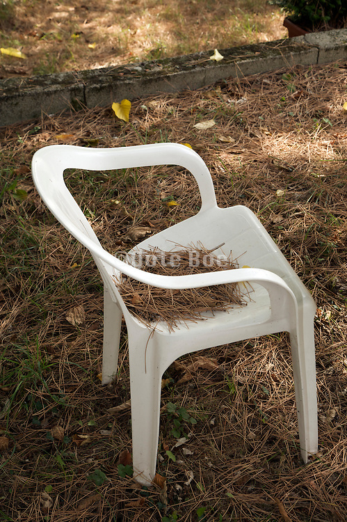 plastic garden furniture with pine needles on the chair