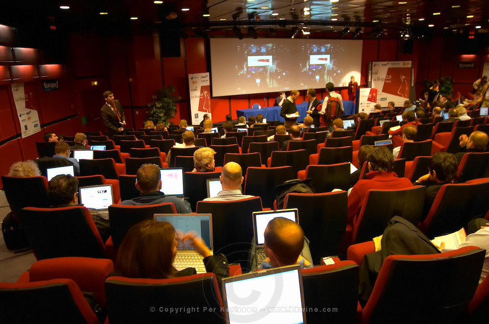 The auditorium amphi amphitheatre with conference participants delegates audience all with laptop computers connected with wireless internet chatting and commenting on the debate online, screens and laptops scattered in the room, at the Les Blog conference in Paris December 2005 on blogging, new media and internet strategy