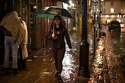 © Licensed to London News Pictures. 20/10/2021. London, UK. A woman shelters under an umbrella as she walks during heavy rain in Greenwich South East London. An Amber weather warning for rain is in place for parts of London and South East England.  Photo credit: George Cracknell Wright/LNP