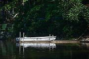 Single white rowboat at wooden dock on lake