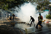 26 DECEMBER 2013 - BANGKOK, THAILAND:  Protestors try to put out a tear gas grenade launched at them by Thai riot police. Thousands of anti-government protestors flooded into the area around the Thai Japan Stadium to try to prevent the drawing of ballot list numbers by the Election Commission, which determines the order in which candidates appear on the ballot of the Feb. 2 election. They were unable to break into the stadium and ballot list draw went as scheduled. The protestors then started throwing rocks and small explosives at police who responded with tear gas and rubber bullets. At least 20 people were hospitalized in the melee and one policeman was reportedly shot by anti-government protestors.     PHOTO BY JACK KURTZ