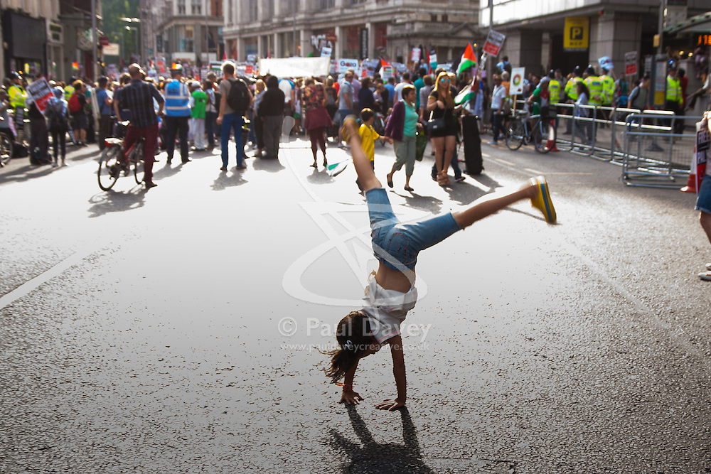 London, August 1st 2014. A bored Leela Harris does cartwheels in the closed-off Kensington High Street as thousands of Palestinians and their supporters protest in London outside the Israeli Embassy following the collapse of the 72 hour ceasefire.