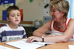 Special needs teacher in classroom with young boy,