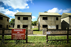 A sign warns the public not to enter empty buildings in Imber village on Salisbury Plain, Wiltshire, where residents were evicted in 1943 to provide an exercise area for US troops preparing to invade Europe. Roads through the MoD controlled village are now open and will close again on Monday August 22.
